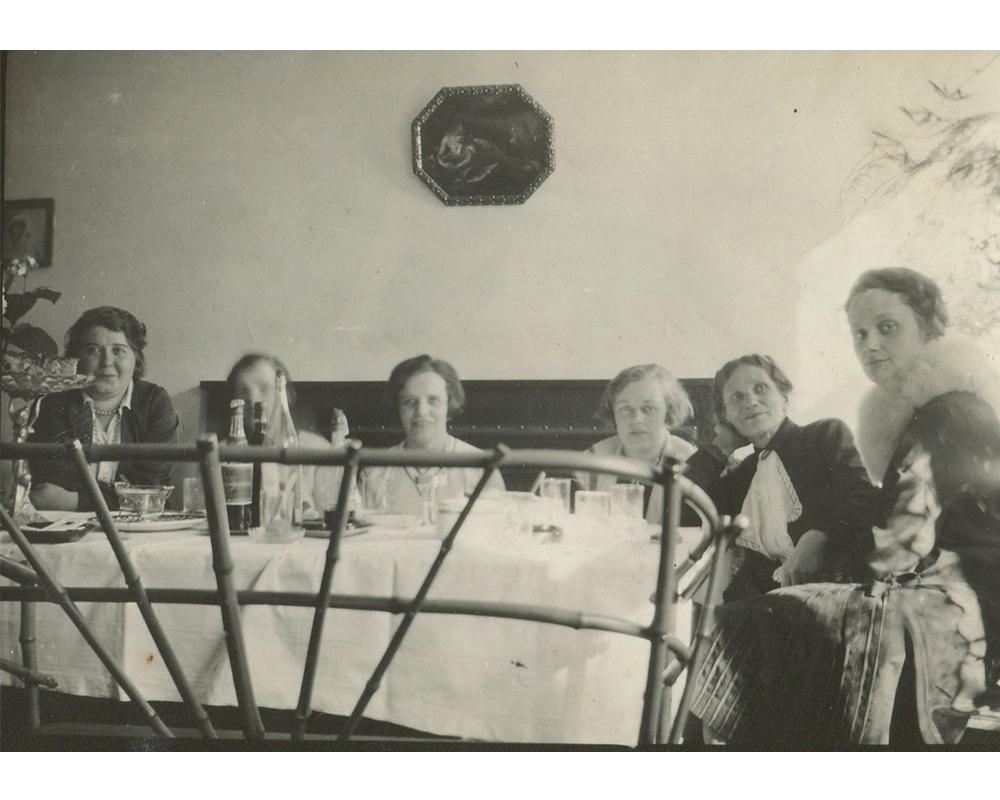 Biesiada sześciu osób za stołem nakrytym białym obrusem
